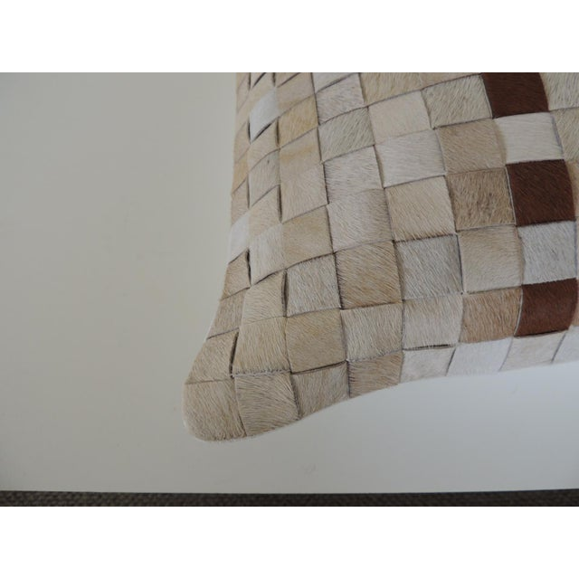 Tan and brown cowhide basket weave decorative pillow. Natural color cotton backing, zipper closure. Soft poly filled...