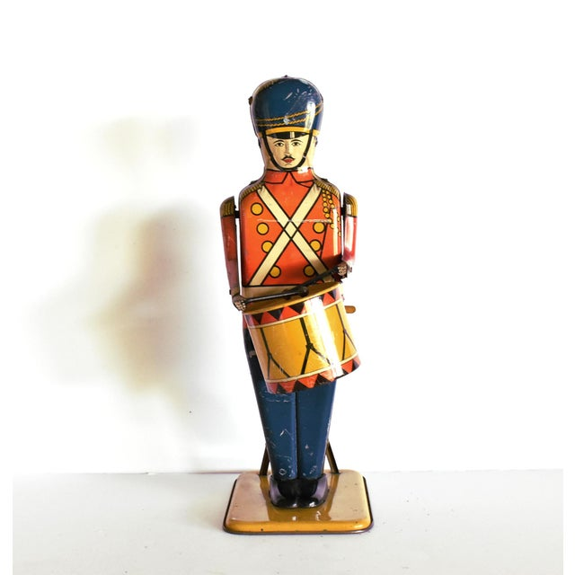 An antique lithograph tin wind-up toy, working, of a drum major in a red-orange coat, navy trousers, and blue hat, with a...