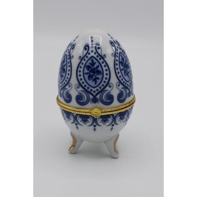 Royal blue floral egg-shaped ring box with lovely paisley design against white background. Ring box has a brass flower-...