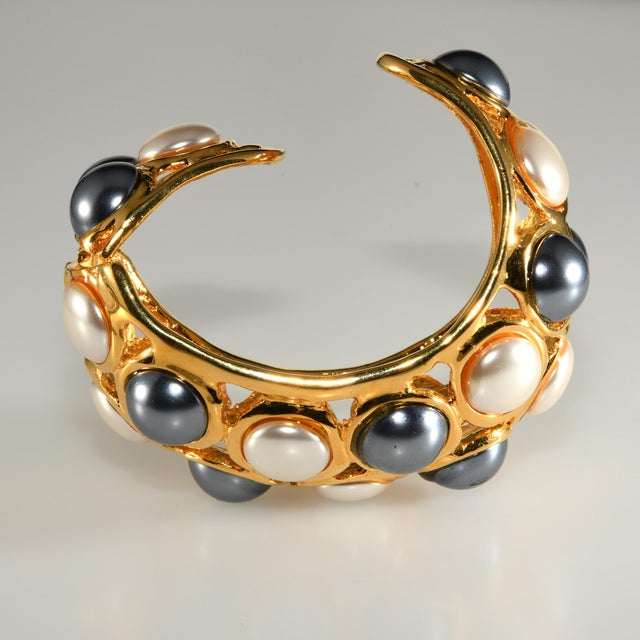 Kenneth Jay Lane hinged cuff bracelet with white and gray faux pearls set in gold plated metal. Domed in shape giving it...