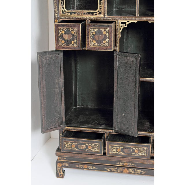 A pair of Chinese black lacquer and gilt display cabinets. A variety of open shelves and closed cubbyholes with doors and...