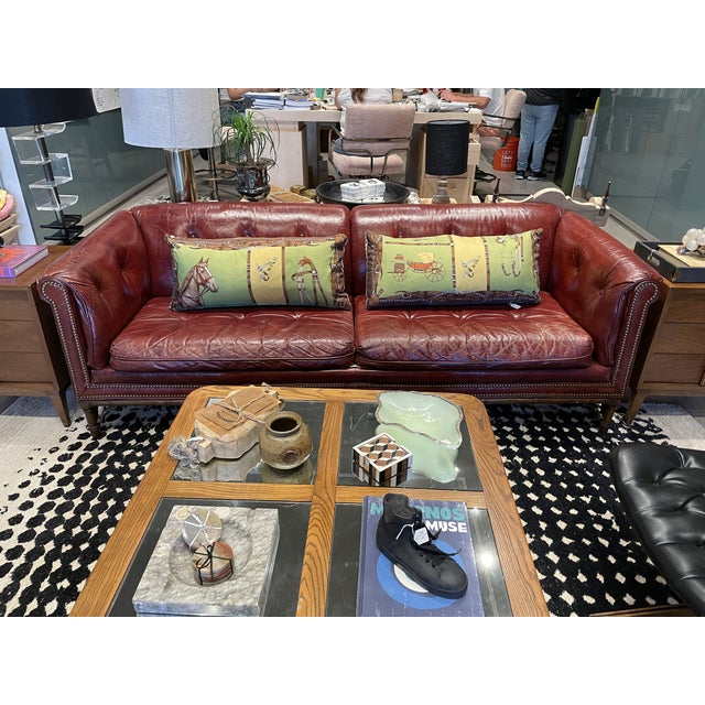 An impressive tufted leather Chesterfield sofa in cherry. Unique Wooden faux bamboo frames with brass bracket leg supports.
