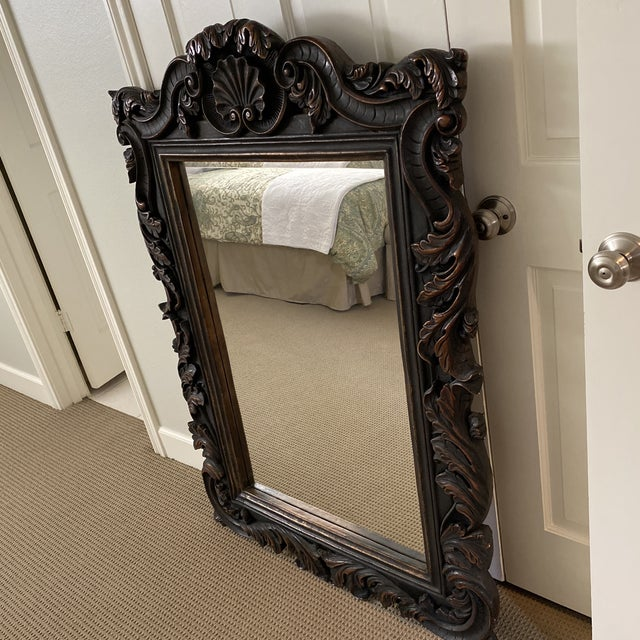 Large ornate wall mirror. Composite material that looks like carved wood.