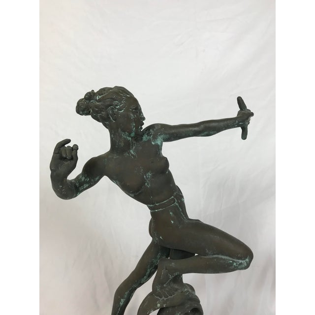 Sheet bronze with weighted base sculpture depicting the goddess Diana. Titled Diana the Huntress this was composed by the...