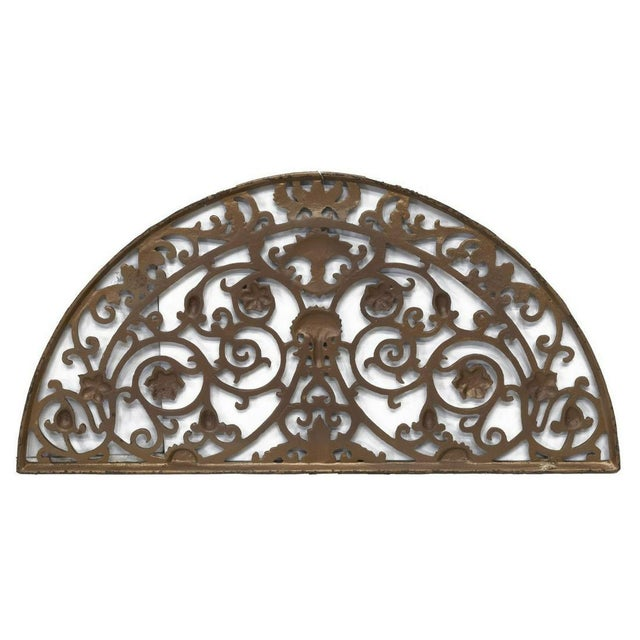 Architectural gold painted cast iron lunette panel, with openwork scrolling foliate, floral, and shell motifs. Dimensions...