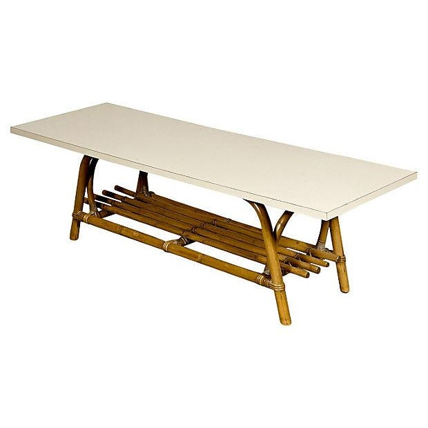 Offered is a white laminate top and rattan wood base coffee table circa 1960s. The table features a built-in magazine...
