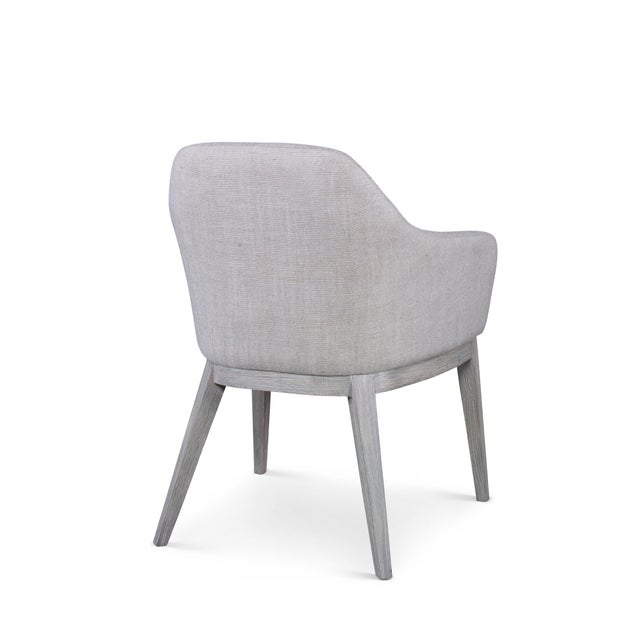This piece is available only as shown, and will ship in 2-3 weeks. An elegant dining arm chair crafted of Grey Oak...