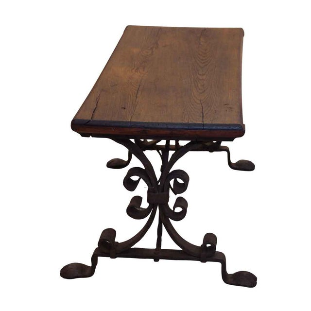 Dark wood tone bench with wrought iron legs. Made in the mid 20th century.