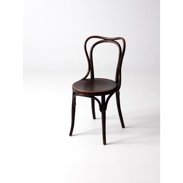 This is an antique bentwood chair by Jacob & Josef Kohn from the late 1800s. The dark bentwood chair features a decorative...