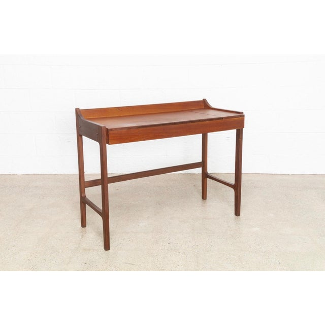This vintage mid century Danish Modern teak vanity table circa 1960 has an elegant, minimalist design with clean lines and...