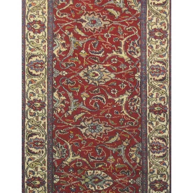 This beautiful rug is hand made, made in Iran. It features a pattern in a vibrant combination of red, navy,blue, purple....