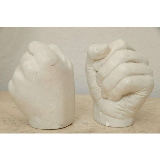 Each fist grasps a taper in this whimsical pair of cast plaster candlesticks by Richard Etts. Signed.