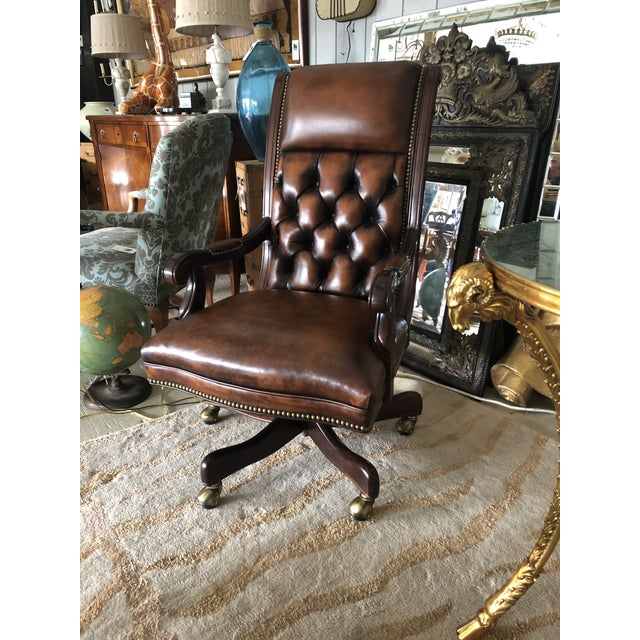 A sumptuous tufted leather super comfortable and rich looking desk chair having curved wooden arms and solid swivel wooden...