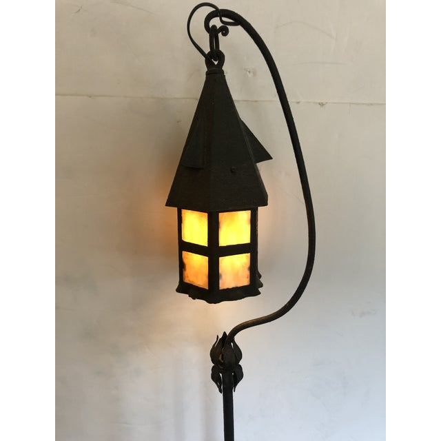 A charming wrought iron and tole Arts and Crafts style floor lamp having a birdhouse shaped whimsical hanging lantern with...