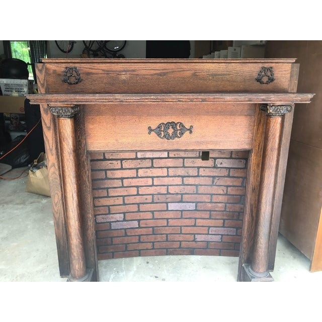 Early 20th century fireplace mantel with surround in mahogany wood. This ornate design with two pillars in a dark cherry...
