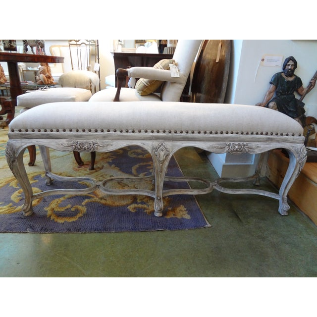 Versatile French Louis XIV style painted bench. Newly upholstered in oatmeal linen with brass spaced nail head trim. Circa...
