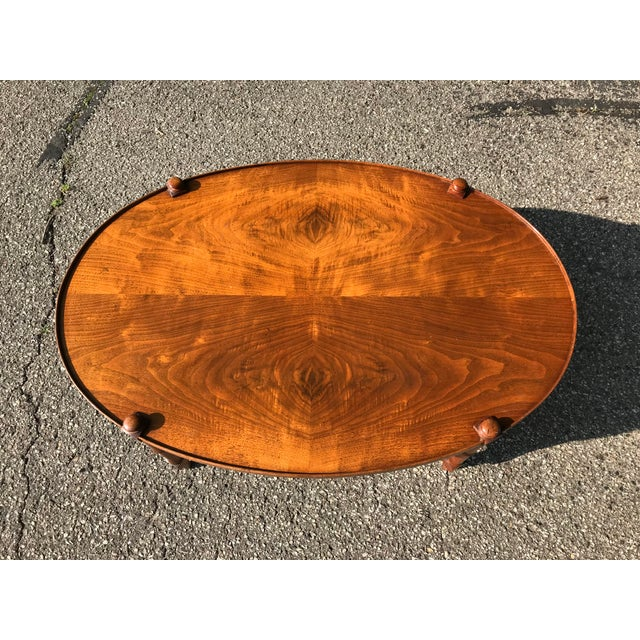 High end walnut coffee table with modern oval design and faux bamboo legs. Likely made by Kindel or baker furniture as...