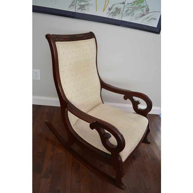 Antique Victorian rocking chair made of solid mahogany and covered in an ivory fabric. Belonged to sellers's grandmother....
