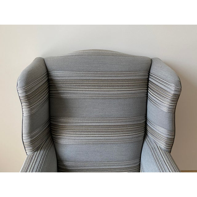 Listed is a masculine and traditional, 1970's wingback armchair. This classic piece has recently been reupholstered in a...