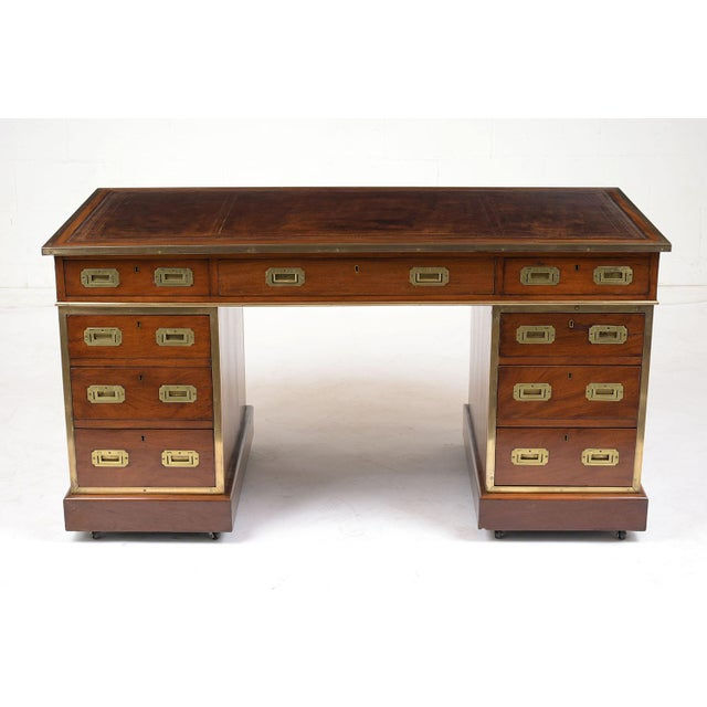 This 1900's English Campaign-style pedestal desk is made of mahogany wood stained a light walnut color with a polished...