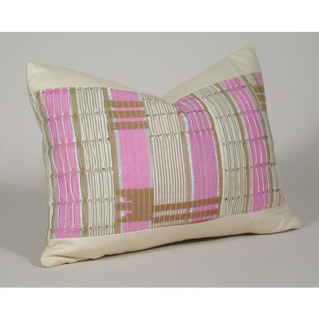 Ivory, beige and pink stripes accented with silver metallic thread, geometric motifs and threaded eyelet detail grace the...