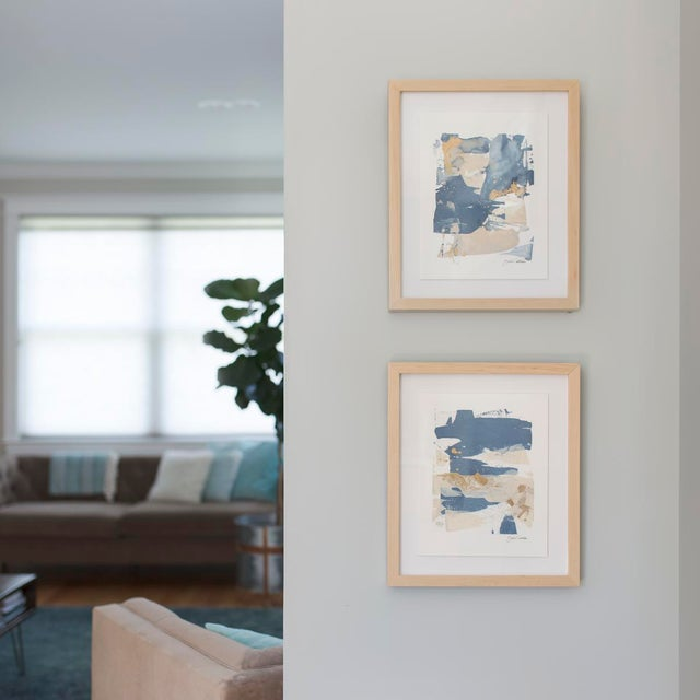 An original abstract painting on paper, composed of blue, beige and metallic gold. Float mounted and framed in a solid...