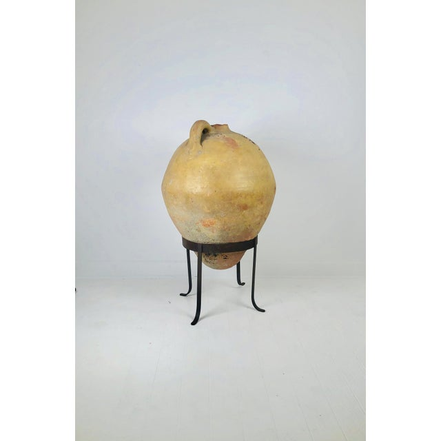 A large one handled Spanish amphora in a later custom steel stand, 14th Century or earlier.