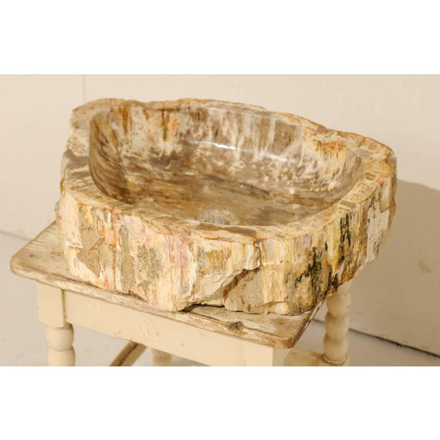 A brown and tan color petrified wood sink. This petrified wood sink features a rounded shape with flatter back-side. The...