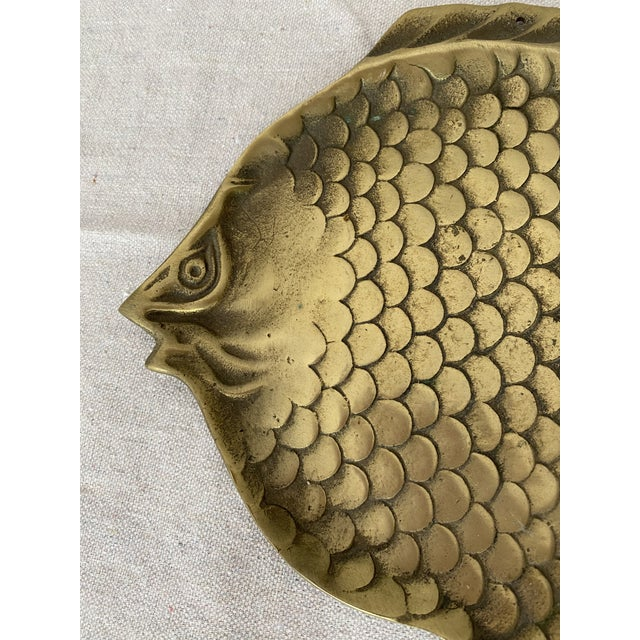 Mid century brass fish plate. Perfect as a catchall for jewelry or keys. Has hole on top to be hung on the wall.