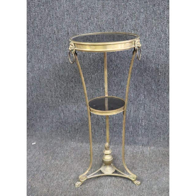 Regency Style Gueridon Table , made of brass , lion mask accents , paw feet , black marble top and lower shelf