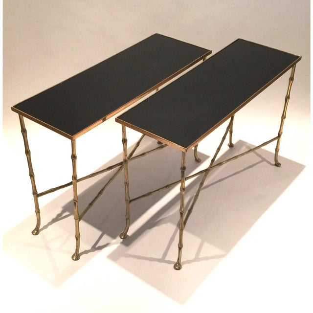 A pair of vintage gilt metal bamboo tables with black glass tops in the style of Maison Bagues.