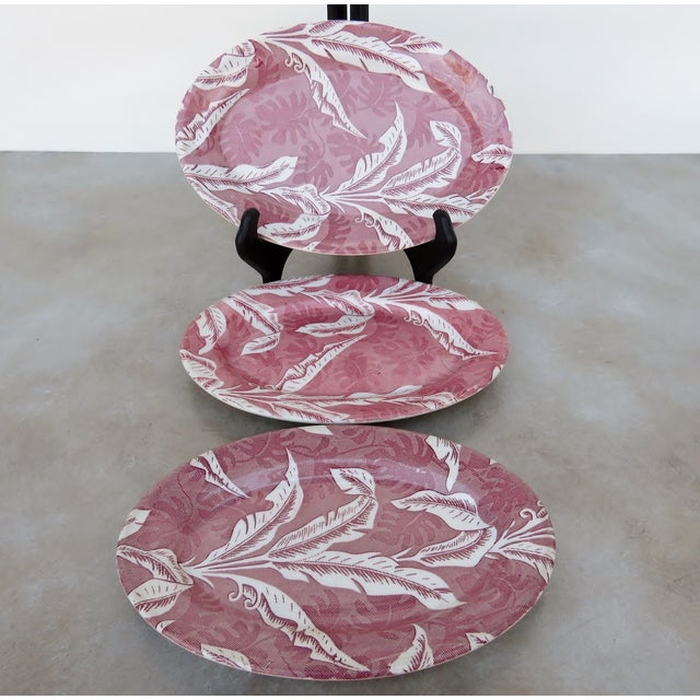 Vintage Tepco tableware in maroon on white hibiscus, magnolia and palm leaf patterns. Set includes 3 platters, in two...