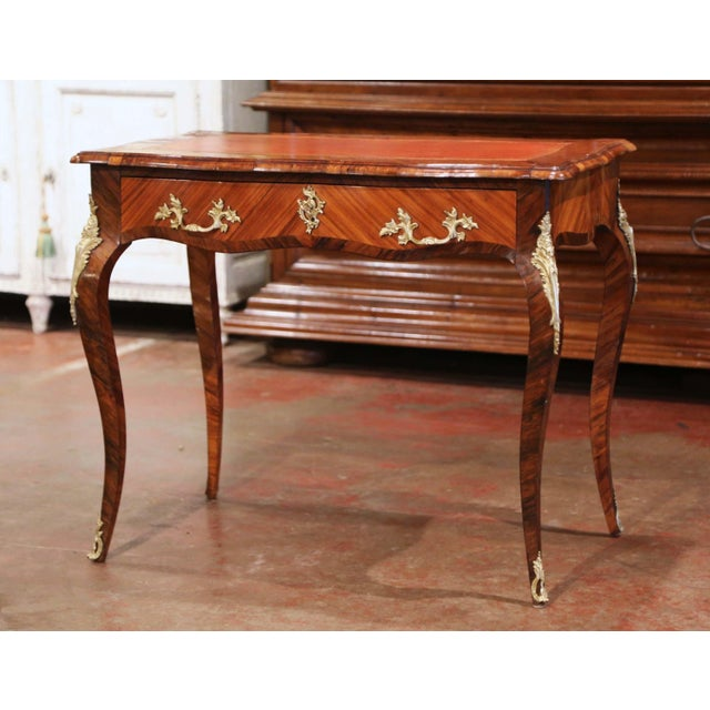 This elegant antique rosewood table was crafted in France, circa 1850. The writing table with serpentine front and bombe...