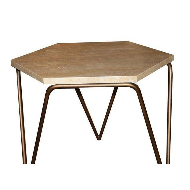 Tom tripod hexagon table shown in satin brass with natural polished travertine top. Custom orders have a lead time of 2-8...
