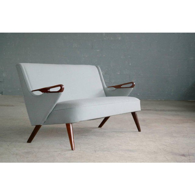 Very rare and simply stunning 1950s sofa attributed to Sven Skipper. The beautifully sculpted armrests in teak evoke...