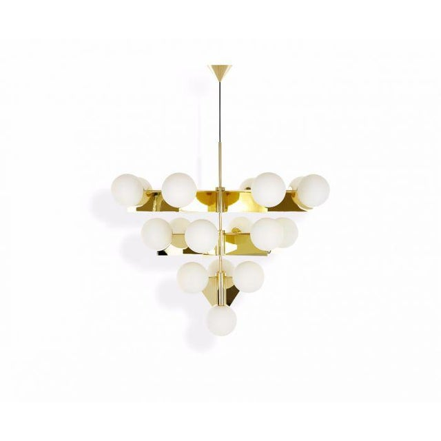 A brass-plated statement chandelier comprising of 4 double-layered white glass spheres distributed over four tiers. This...