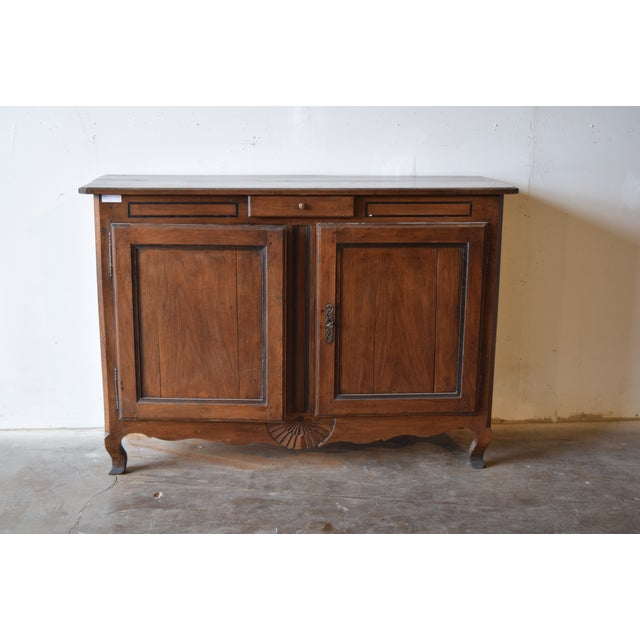 18th century French buffet. Built of oak, a single drawer sits over double paneled cupboard doors that feature iron fiche...