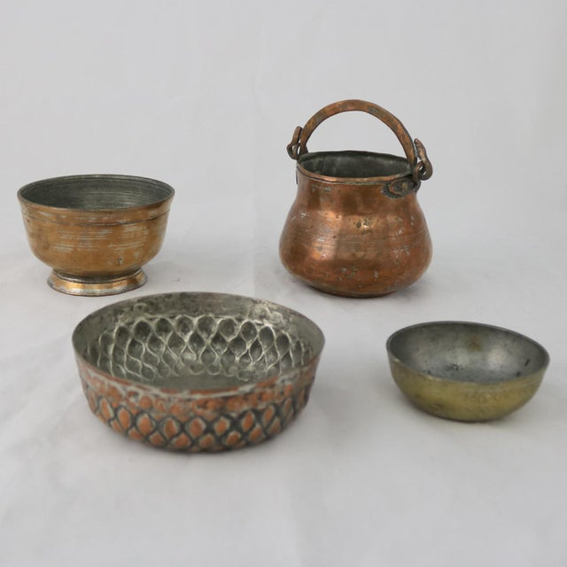 Wonderful set of four antique Turkish copper and brass bowls and pot. They are hand forged, hand incised with gorgeous...