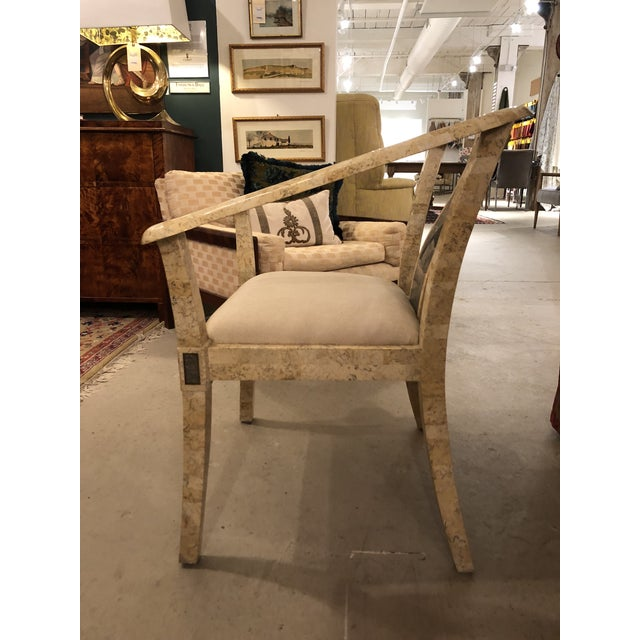 Occasional chair made of cream colored stone with faux snake skin cream seat.