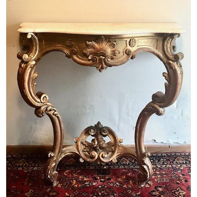 An antique Louis XV style hand carved and gilded 19th century console with an original serpentine white marble top. It is...