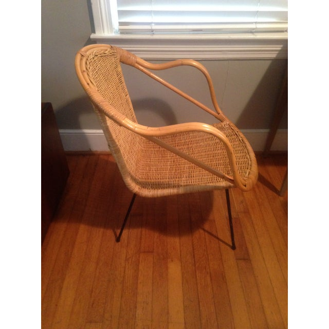 This chair makes wicker look modern. It has black, metal legs and a cool shape.