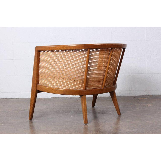 A mahogany and cane lounge chair with original white leather. Designed by Harvey Probber.