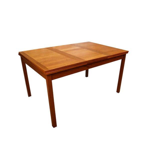 Exceptional Danish Modern teak extension dining table. In the style of Arne Vodder. With an initial small footprint, this...