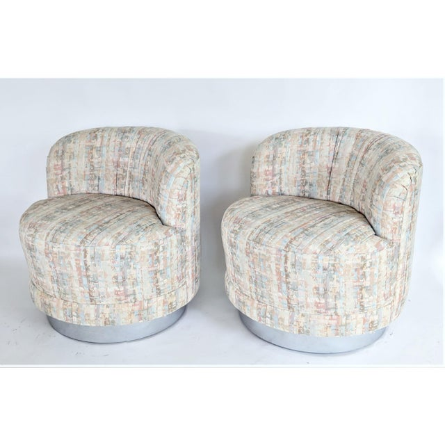 Beautiful swivel tub chairs upholstered in original fabric of salmon, rose, teal, and beige colors. Upholstery is in...
