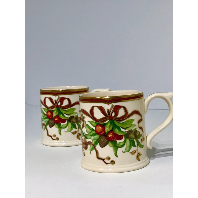 A stunning pair of mugs by Tiffany & Co. Garland Pattern. These holiday china coffee mugs feature cranberries - pine cones...