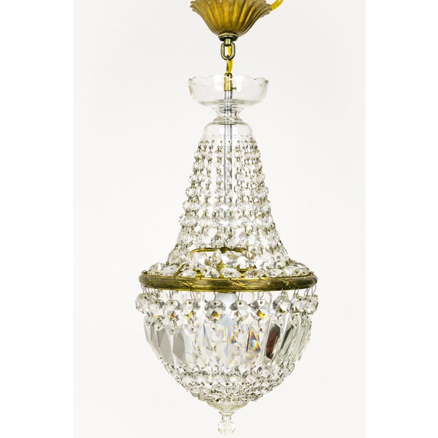 These Regency Style chandeliers from the 1920's have radiant, closely placed crystal strands forming its basket shape. A...