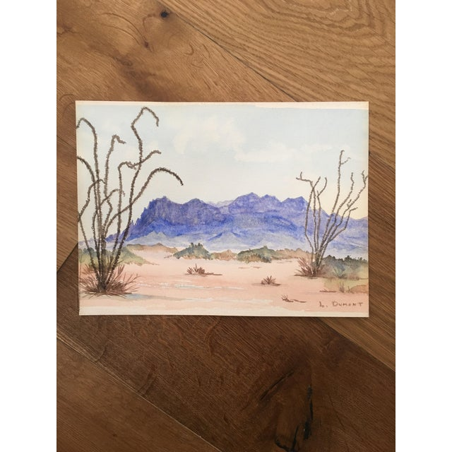 """A vintage watercolor painting of the desert. The painting is signed """"L. Dumont."""