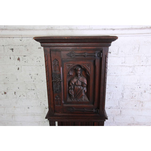 Offering a very nice 19th Century Belgian dark walnut gothic bar cabinet. The cabinet has a carved religious figure giving...