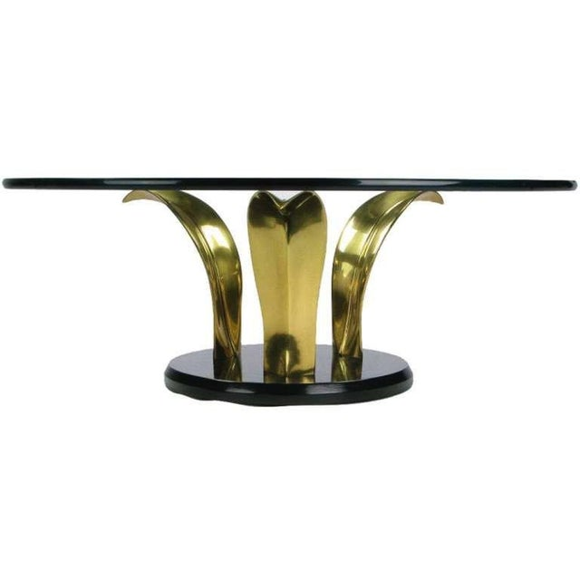 A striking round cocktail table reminiscent of organic design. The base is comprised of three large brass palm leaves and...