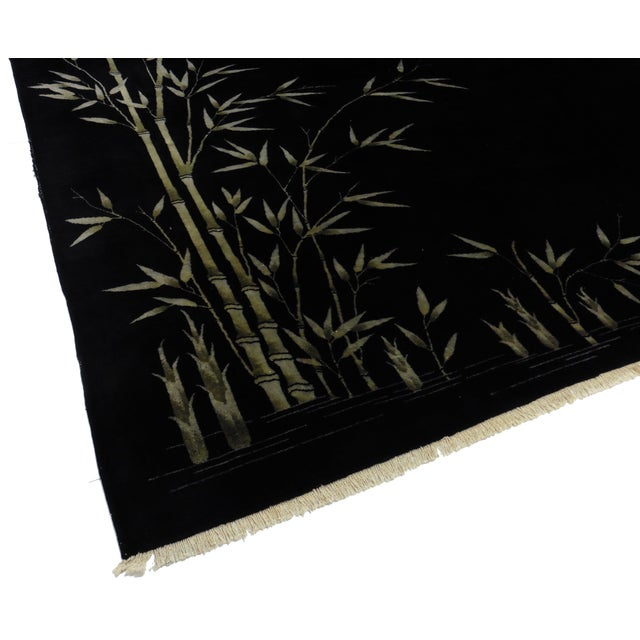 This particular rug is quite simple yet holds such an elegant feeling. It has an all-black background with a few bamboo...